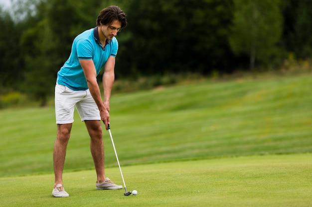 Erwachsener mann des vollen schusses, der draußen golf spielt