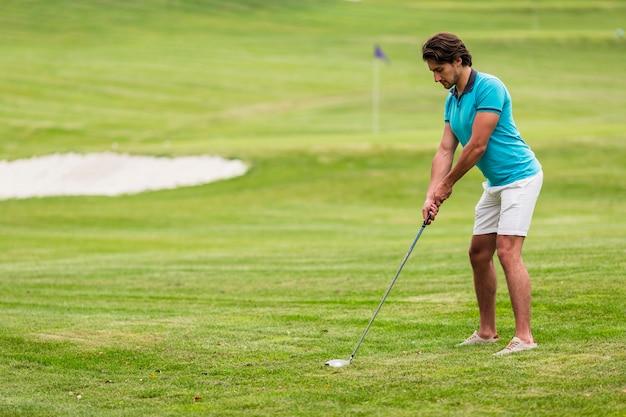 Erwachsener mann des vollen schusses, der golf spielt