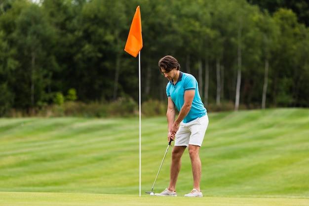Erwachsener mann des vollen schusssitzes, der golf spielt