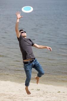 Erwachsener mann fangen frisbee am strand