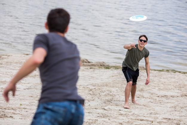 Erwachsener mann frisbee für freund am strand werfen