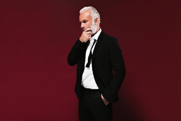 Erwachsener mann im anzug posiert nachdenklich an burgunderfarbener wand