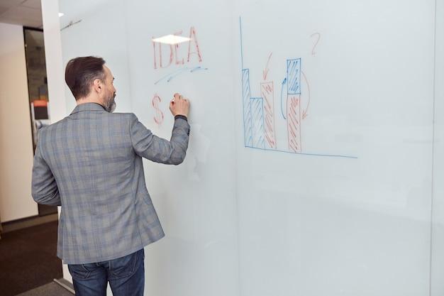 Erwachsener mann im büro schreibt auf den glasschreibtisch