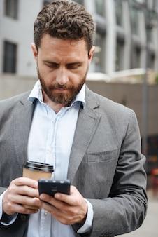 Erwachsener mann im grauen anzug, der textnachricht im mobiltelefon tippt oder liest, während er mit kaffee zum mitnehmen vor dem modernen geschäftszentrum steht