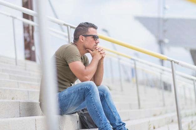 Erwachsener mann im grünen t-shirt, das draußen draußen auf der treppe und im denken sitzt