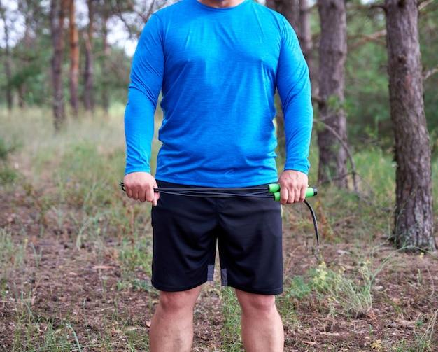 Erwachsener mann in der blauen kleidung, die ein seilspringen für das spielen des sports hält