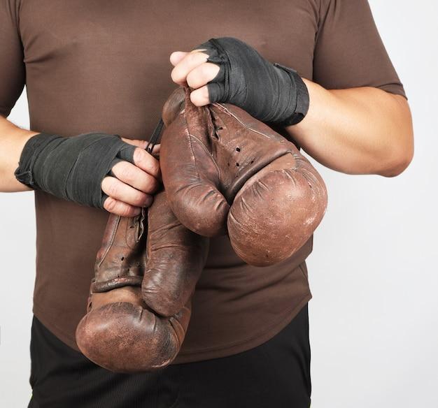 Erwachsener mann in der braunen sportuniform hält ein paar zufällige boxhandschuhe der braunen weinlese
