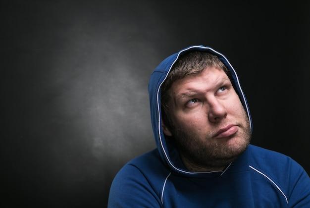 Erwachsener mann in der haube sitzt denkend