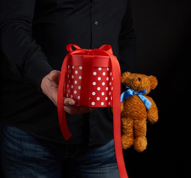 Erwachsener mann in einem schwarzen hemd hält eine blaue quadratische schachtel, die mit einem roten band gebunden wird
