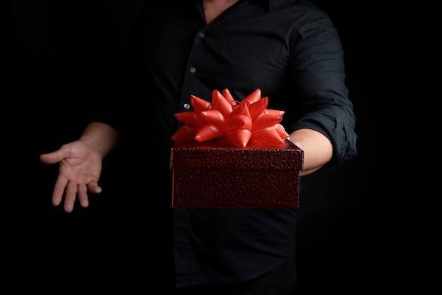 Erwachsener mann in einem schwarzen hemd hält einen kasten des roten quadrats mit einem geknoteten bogen