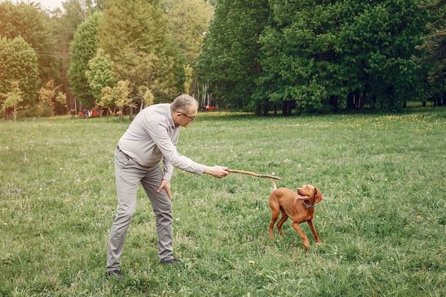 Erwachsener mann in einem sommerpark mit einem hund
