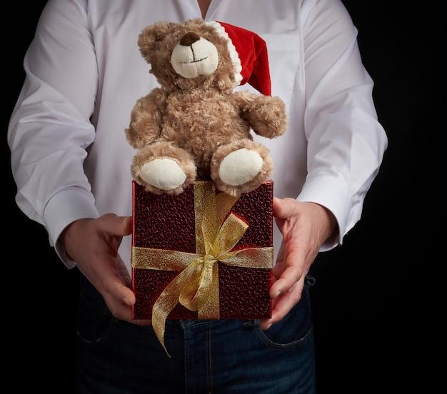 Erwachsener mann in einem weißen hemd hält einen kasten des roten quadrats, der mit einem goldenen band und einem braunen teddybären gebunden wird