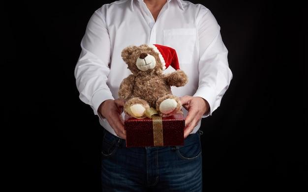 Erwachsener mann in einem weißen hemd hält einen kasten des roten quadrats, der mit einem goldenen farbband gebunden wird