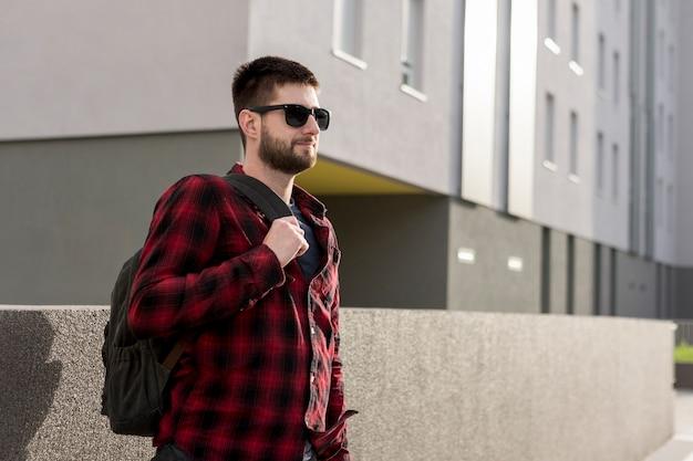 Erwachsener mann in freizeitkleidung mit rucksack