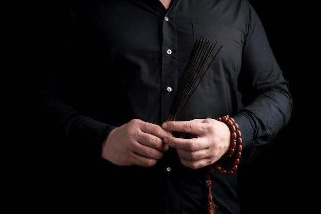 Erwachsener mann in schwarzer kleidung hält einen stapel räucherstäbchen