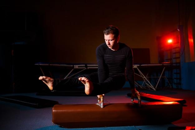 Erwachsener mann in sportkleidung macht übungen an gymnastikgeräten in der akrobatischen turnhalle