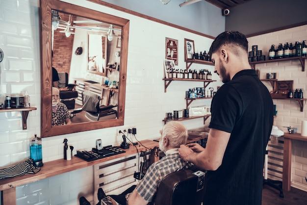 Erwachsener mann kam zum jungen friseur für art-haarschnitt