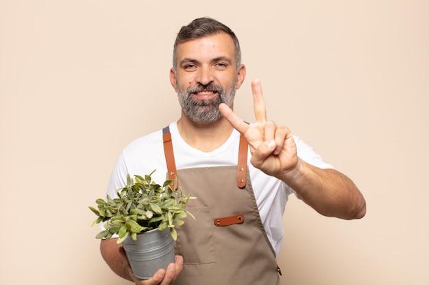 Erwachsener mann lächelt und sieht freundlich aus, zeigt nummer zwei oder sekunde mit der hand nach vorne, countdown