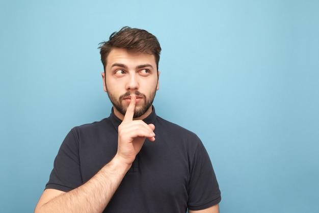 Erwachsener mann mit bart, der nachdenklich zur seite zu einer leeren stelle schaut und ein zeichen der stille zeigt, das einen finger nahe seinem mund auf blau hält