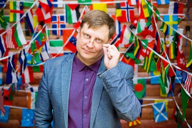 Erwachsener mann mit brille vor dem hintergrund der flaggen verschiedener staaten.