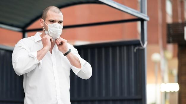 Erwachsener mann mit chirurgischer maske, die auf den bus wartet