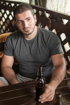 Erwachsener mann mit dem bier, das in der stange sich entspannt