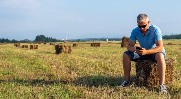 Erwachsener mann mit einem telefon sitzt auf einem heuhaufen.