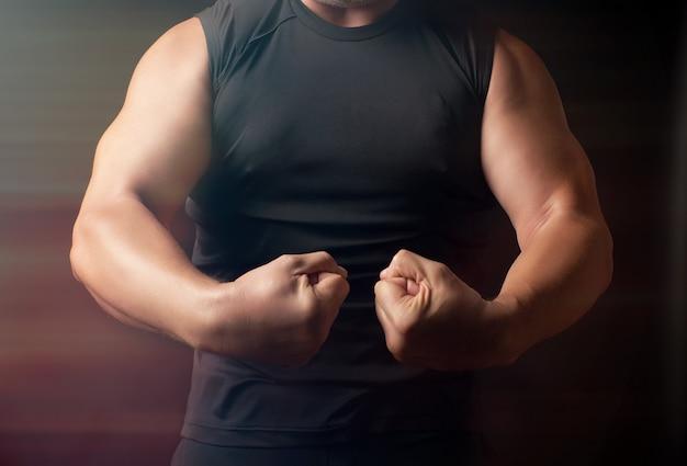 Erwachsener mann mit einer sportfigur in schwarzer kleidung spannte seine muskeln in seinen armen