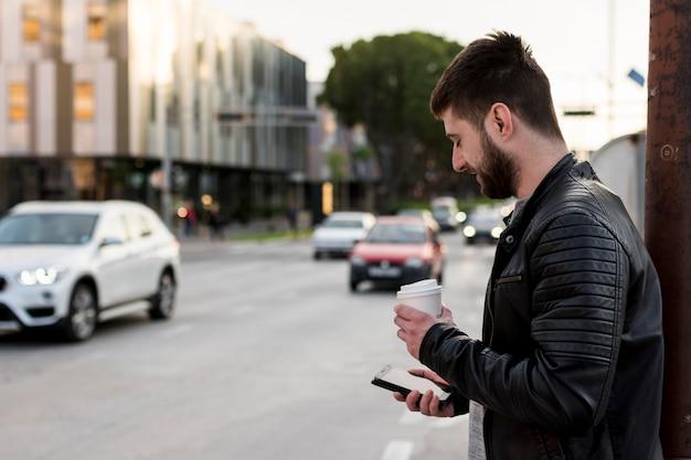 Erwachsener mann mit kaffee unter verwendung des handys
