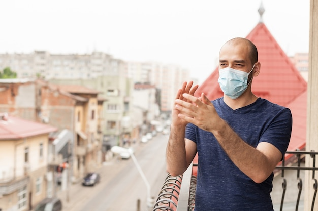 Erwachsener mann mit schutzmaske, der auf balkon klatscht und unterstützung für medizinisches personal im kampf mit coronavirus zeigt.