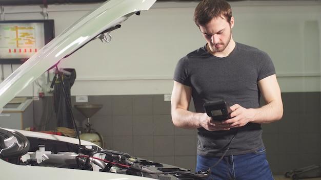 Erwachsener mann prüft den zustand des fahrzeugs in einer reifenservice-werkstatt.