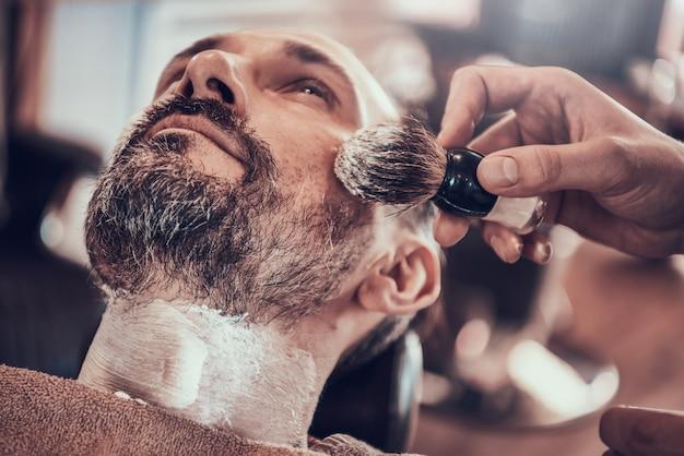 Erwachsener mann rasieren in einem stilvollen friseursalon