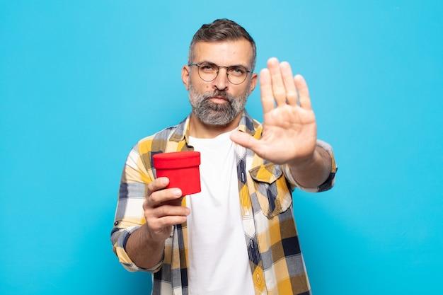 Erwachsener mann sieht ernst aus und hält eine geschenkbox holding