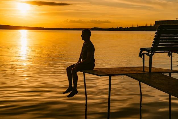 Erwachsener mann sitzt auf dem mauerwerk mit einer bank