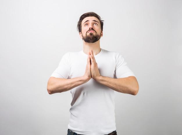 Erwachsener mann steht auf dem boden und betet. während er das gebet spricht, schaut er auf. dieser typ ist wahrscheinlich ein gläubiger. isoliert auf weiße wand.