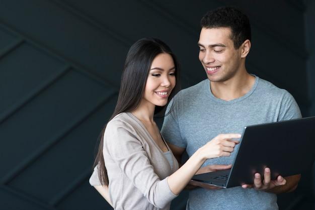 Erwachsener mann und frau, die zusammen an einem laptop arbeiten