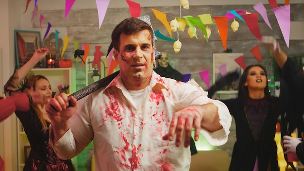 Erwachsener mann verkleidet als zombie mit einer axt auf einer halloween-party.