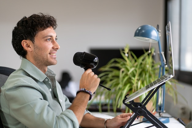 Erwachsener mann zeichnet einen podcast von zu hause, digitales hausarbeitskonzept, junger unternehmer auf