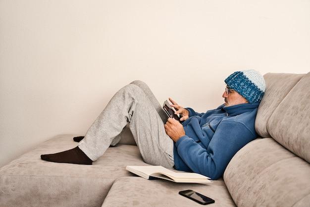 Erwachsener mit brille, kurzem bart und mütze auf dem grauen sofa