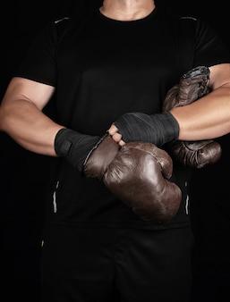 Erwachsener muskulöser mann in der schwarzen kleidung zieht lederne braune boxhandschuhe an seinen händen an