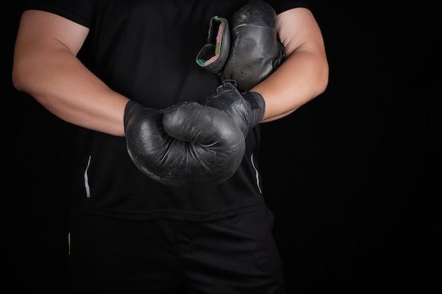 Erwachsener muskulöser mann in der schwarzen kleidung zieht lederne schwarze boxhandschuhe an