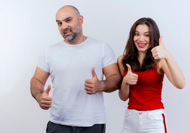 Erwachsener paar selbstbewusster mann und beeindruckte frau, die beide daumen hoch zeigen und schauen