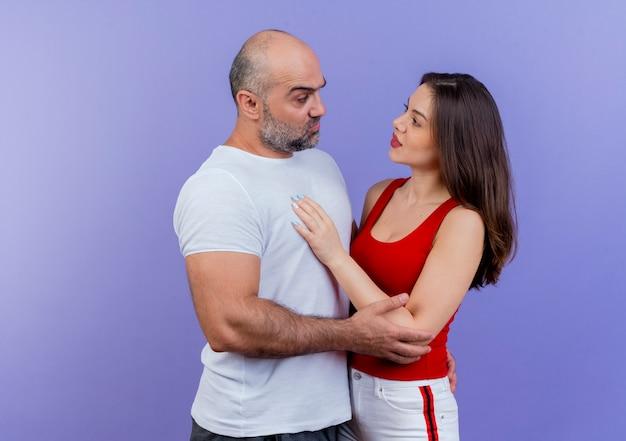 Erwachsener paar zweifelhafter mann legt hand auf den rücken der frau und berührt ihren arm und sie legt hand auf seine brust beide schauen sich an