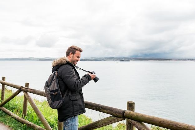 Erwachsener reisender in freizeitkleidung und stirnband, der das plätschernde meer vor der kamera fotografiert