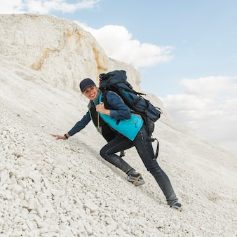 Erwachsener reisender mit dem rucksackklettern
