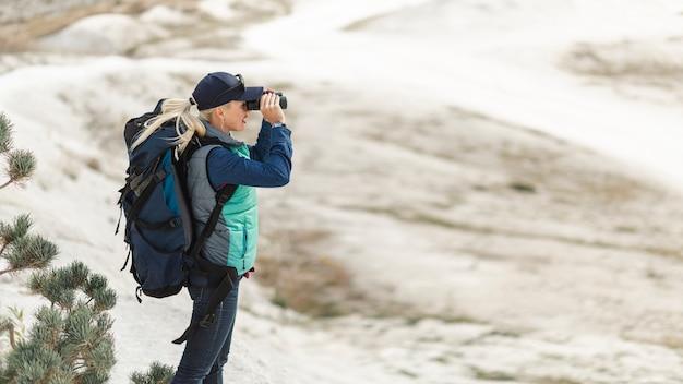 Erwachsener reisender mit rucksack und fernglas