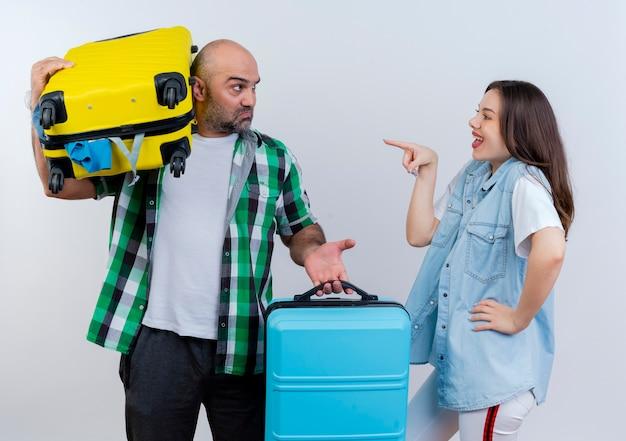 Erwachsener reisenderpaar unzufriedener mann, der koffer hält, einer von ihnen auf schulter freudige frau, die hand auf taille hält und auf ihn zeigt beide, die einander ansehend betrachten