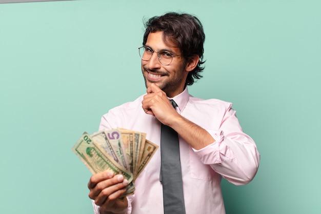 Erwachsener schöner indischer geschäftsmann mit dollarbanknoten
