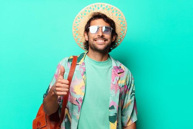 Erwachsener schöner indischer touristenmann, der heu und eine ledertasche trägt