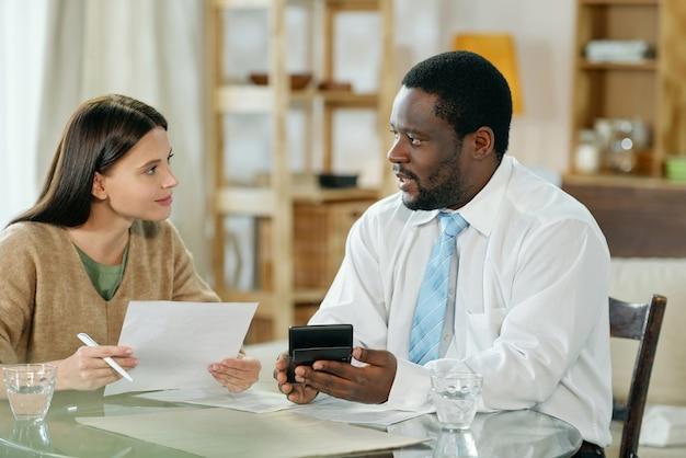 Erwachsener schwarzer mann und junge frau, die am tisch sitzen und wohnungsbaudarlehen mit papieren besprechen